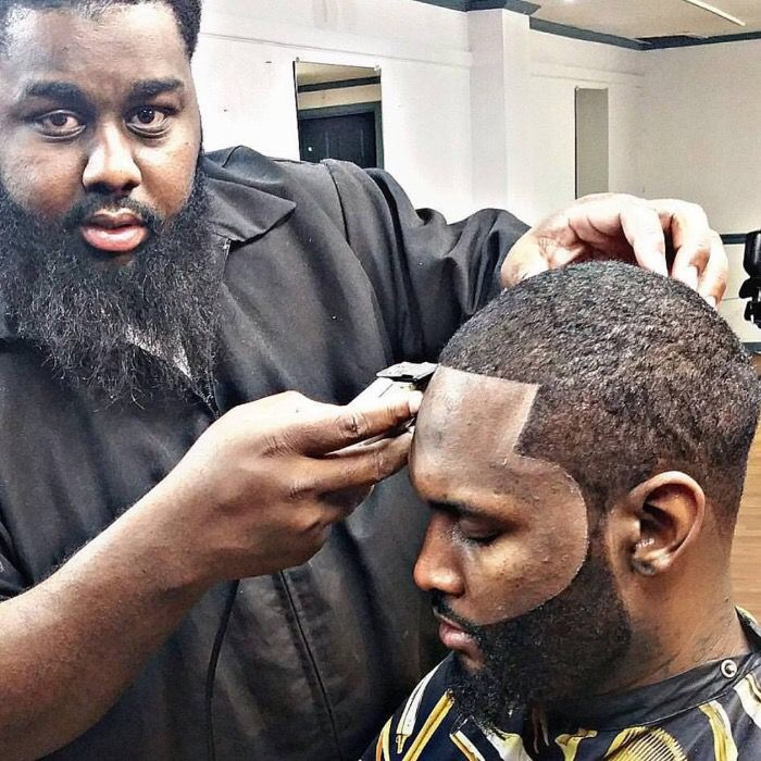 Willie Walker prepares to cut the hair of Nathaniel Tucker Tuesday in the barber  school at